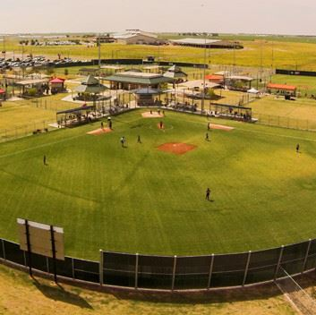 An overhead view of a baseball diamond with kids playing a match